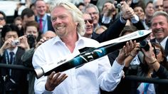 Richard Branson shows a model of Launcher One to the crowd during a photocall for the Virgin Galactic, the world's first commercial spaceline, at the Farnborough International Airshow in Hampshire, England, July 11, 2012.