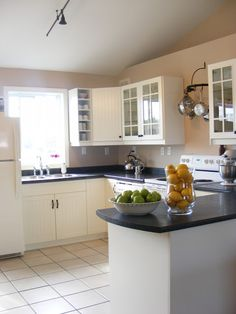 HOW TO STAGE A KITCHEN - Take everything off the kitchen counter tops that you don't absolutely have to use every single day! (there are a couple of essentials in this picture) Next - Put out some colorful fruit on the counter top. Finally - Kitchen must be sparkling clean! These are the kinds of things you need to do to increase buyer appeal and maximize the price you can get for your home.