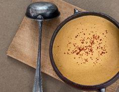 Für die goldene Maiscremesuppe mit Chiliflocken Zwiebeln häuten, fein würfeln und in einem Topf in Öl andünsten, Chiliflocken