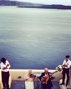 Musicians playing for the newly weds, with spectacular views of the volcano in the picturesque village of Oia in Santorini island, Greece - selected by www.oiamansion.com