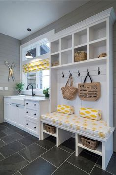 laundry room idea. Love the grey tile with white cabinets. Bench and lockers. Planked grey walls. Laundry room inspiration.
