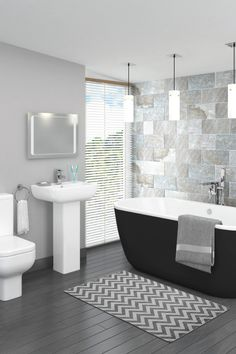 Want the modern grey bathroom look in your home? This stunning contemporary grey bathroom design includes a black freestanding bath, a freestanding bath tap and short-projection toilet and basin. Other grey bathroom ideas on show include grey bathroom tiles, dark wood effect flooring and a back lit bathroom mirror. Click the image for more information.