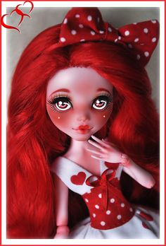 Monster High Draculaura repaint. Draculaura's been rerooted with soft fluffy red hair, and red eyes, eyebrows, and cupid's bow mouth, as well as red blushing on her cheeks and nose. There's a single white dot on the center of each cheek. She's wearing a red and white polka dot bow in her hair, and a red and white dress in a matching polka dot pattern and complimentary heart pattern. By Clockwork_Angel.