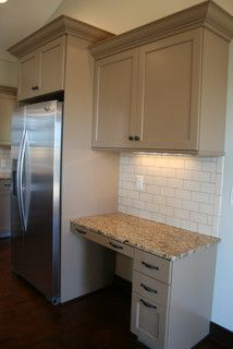 Tan Painted Cabinets With Granite Tops And Subway Tile.