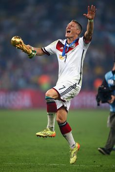 Bastian Schweinsteiger of Germany celebrates with the World Cup trophy after defeating Argentina 1-0 in extra time during the 2014 FIFA World Cup Brazil Final match between Germany and Argentina at Maracana on July 13, 2014 in Rio de Janeiro, Brazil