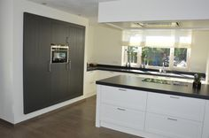 Keuken in modern landelijke stijl. Met kook schiereiland en ingebouwde kast met inbouwapparatuur. Combinatie van wit met donker. Gemaakt door Geert Bouten Interieur op maat