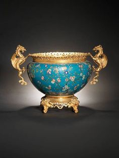 A large cloisonné enamel and gilt-bronze jardinière, 19th century. photo Bonhams Of bombé form, finely enamelled around the sides with a multitude of butterflies in flight amidst blossoming peonies and prunus, all on a turquoise diaper ground, with a ruyi-head border at the rim, the base and mouth with European gilt-bronze mounts. 74.4cm (29¼in) wide across handles. Estimate: £8,000 - 10,000, HK$ 95,000 - 120,000