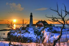 Portland Head Light in Cape Elizabeth, Maine as the sun just clears the horizon to cast a brilliant light of purple, pink and yellow hues over a snow covered winter landscape. #PortlandHead #Maine #Lighthouse