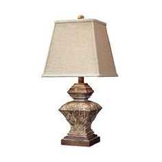 "Antiqued geometric-shaped table lamp with leaf accents.     Product: Table lampConstruction Material: Composite and fabricColor: Natural and ivoryAccommodates: (1) 60 Watt med bulb - not includedDimensions: 23.5"" H x 11"" W x 11"" D"