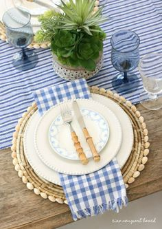 For this table setting, the casual stripes and gingham remind me of summer picnics and barbecues. A fun succulent arrangement and seashell accented placemats bring to mind fun times spent at the beach. Remember to decorate with what you love and what make
