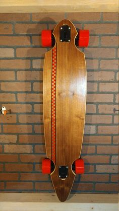 For sale is a beautiful 42 walnut longboard with a red checkered stripe on top and a vintage bottle cap print bottom. The board is made of 9 alternating layers of maple, berch, and bamboo with a top layer of walnut. The bottom is bottle cap print fabric inbeded in epoxy. Dimensions are