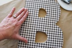 DIY wooden letters with scrapbook paper.  Maybe paint the letter beforehand to make the wood less visible?
