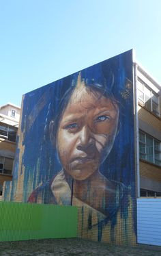 """Contribution to the """"Wall to Wall"""" project by Adnate. It depicts a young Burmese girl, and was painted as part of the Benalla Street Art Festival in January 2015. The work was painted on the middle section of the old local SEC offices, now the NEA - North East Artisans."""