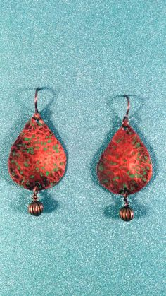 These earrings were cut from copper sheet then hammered. A green patina was added and then an all over patina was added to enhance the glow