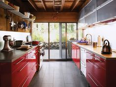 Bates Masi, kitchen with red Ikea cabinets and blue sandstone tiled floor