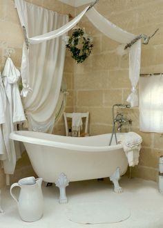 .Beautiful serene clawfoot bathtub surrounded by stone walls and branches that hold up a linen canopy. Such a clean, organic space.