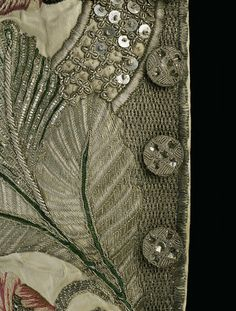 Buttons and embroidery detail of gentleman's sleeved waistcoat, ca.1745, of ivory satin embroidered with silk and silver threads, lined with ivory ribbed silk and fustian. The cuffs of the associated cioat have been added to the waistcoat