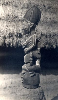 Nigeria, study of carved wooden mask with figure on top. Figure represents adult female carrying young children. Section-view of thatched-roof building in background. Medium: Gelatin silver print.