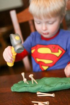 Hammering tees into play dough for toddlers to work on hand and eye coordination