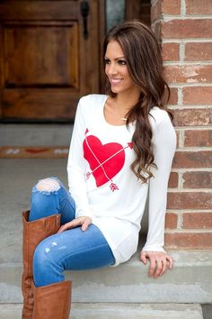 a heart long sleeve top, jeans and high boots