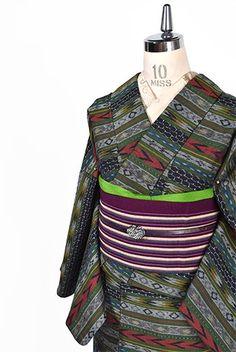 マニッシュなカーキグリーンのカラーリングをアクセントにして、フォークロアムードただよう絣模様が形作るボーダデザインが織りだされたウールの単着物です。