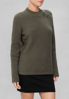 This densly knitted sweater is fashioned from a soft wool blend. Featuring a mock neck and diagonal button closure at front.
