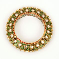 A Diamond Bracelet, Hyderabad, Deccan, 18th Century. A gold bracelet set in the kundan style with flat cut diamonds. One side has quatrefoil flowers interspersed with single leaves set in a blue enamel (nil zamin) ground. The reverse has single diamond leaves set in a green enamel (sabz zamin )ground. On the exterior rim of the bracelet are Basra pearls on the interior a fine band of waterlillies set in white enamel roundels in turn set in dark blue enamel ground.