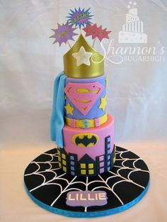 """Girl"" Superhero cake in black, white, gold, pink, purple, light blue, and yellow. 2-tier, fondant covered with Wonderwoman crown, and cardstock Boom! Pow! Crash! toppers. Includes Spiderman, Batman, Superman, and Wonderwoman elements. Chocolate cake, vanilla buttercream, white chocolate ganache frosting."