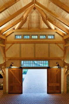Custom mahogany barn doors supported by heavy iron tracks and pulleys provide entry into this luxury garage. Above, detailed woodwork and windows with multiple muntins create a feeling of age. Below, brick flooring looks charming and historic but features radiant heating for an updated touch.