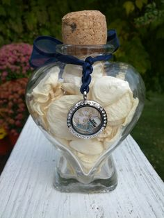 Preserved Bridal Bouquet Bottle.  Dried rose petals from the bridal bouquet in a glass heart shaped bottle.  Charm from bouquet, tied with ribbon from the wedding invitation.  Cork from champagne on the night of engagement.  Voila!