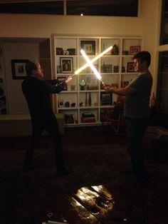 Joss Whedon and Nathan Fillion having a lightsaber battle.