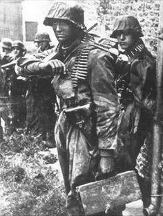 SS-Sturmmann Otto Funk (WIA 26.06.1944), SS-Aufklärungs Kompanie 15, carrying ammo box for MG 42 of SS-Schütze Klaus Schuh, photographied beside another ammo-man, SS-Sturmmann (?), around 2:30 pm in Rots, Normandy. 9 June 1944.