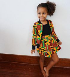 This skirt is make of gorgeous African ankara print fabric - this listing is for a orange red green and black kente fabric. The fabric is cotton, and the back half of the waist band is elasticized for a comfortable fit! Lola is wearing a size in t Baby African Clothes, African Dresses For Kids, Latest African Fashion Dresses, Ankara Fashion, African Kids, African Print Skirt, African Print Dresses, African Print Fashion, Africa Fashion