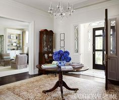 A round table and secretary lend scale to this open entryway - Traditional Home® / Photo: Werner Straube /  Design: Suzanne Kipp
