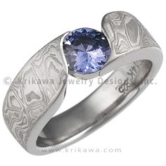 White Mokume Wave Engagement Ring with Blue Sapphire - An organically shaped mokume band that is contoured to a variety of stone shapes. This engagement ring's stone is flush set to the band, which thickens toward the top of the finger to allow for the depth of the stone. - This White mokume solitaire engagement ring is set with a blue sapphire.