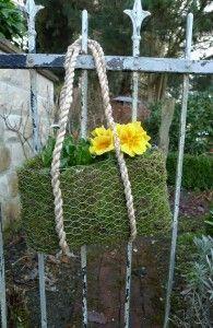 Tasche aus Moos und Hasendraht mit Blumen bepflanzt