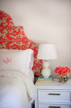 pink and red ikat sculpted headboard, white sheets, pink monogram pillow, white ceramic bubble lamp, coral roses