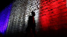 A man walks past Jerusalem's Old City walls illuminated in the colors of the French flag on Sunday, November 15, to show solidarity for France after the deadly terrorist attacks in Paris. Displays of support for the French people were evident at landmarks around the globe.