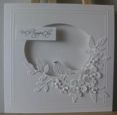 handmade card  from MISSY G DESIGNS: White on White ... oval window cut with lovely montage of die cut and embossed flowers and leaves ... bird too ...