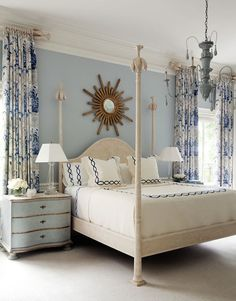 Lovely white and blue bedroom features gold sunburst mirror on blue gray walls over cream four poster bed with camelback headboard dressed in white and blue chain link bedding flanked by blue French nightstands topped with crystal table lamps situated under windows dressed in blue and gray print curtains illuminated by blue candle chandelier.