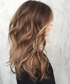 Halfway between blonde and brown, this caramel hair color adds bounce and body to this layered cut #wavyhair #longhair #hairstyle