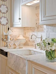 A marble farmhouse-style sink and subway tiles with beveled edges give a small kitchen a serious WOW factor