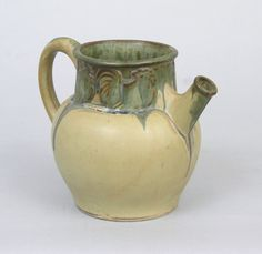 """A Denbac Ewer, French, ca. Early 20th Century. Earthenware ewer, designed with decorative band near the rim depicting cockerels; overall olive-green matte body highlighted with dripping blue glaze. Overall measures . 5-1/2""""H x 7-1/2""""W x 5""""W."""