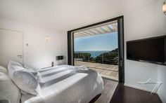 White Second Floor Bedroom Featured with Sliding Glass Door Connecting to Balcony and Bay View of St. Tropez