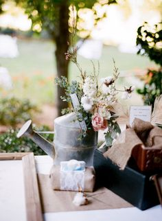 love the watering can flower vehicle - good for gift table, entry table, escort card table...