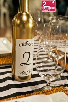 This summer we decided to experiment with wine bottles. Our clients are in Love with this. Why? Cheaper and different. Bottles can be used for different elements. Centerpieces, table number, flower holder, or just props...   Gold, black and white were the colors  www.2republicevents.com