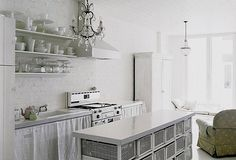 White  rustic kitchen with baroque chandelier.