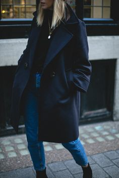 Emma Hill wears black roll neck sweater jumper, navy coat, mom jeans, gold necklaces, black ankle boots, winter outfit