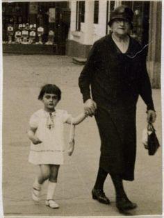 Margot Frank, older sister of Anne Frank, with her grandmother walking in 1929