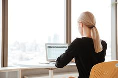 Back view photo of young woman worker sitting in office while using laptop computer.